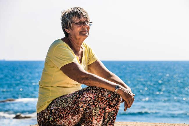 elderly woman sitting alone near ocean