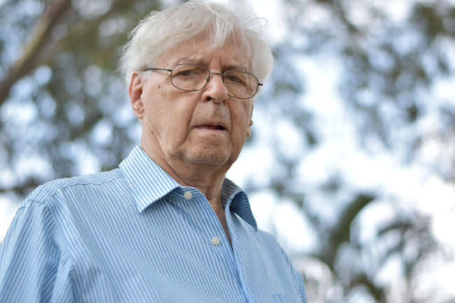 elderly man with a blue shirt and glasses